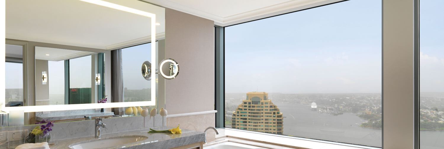 5-star hotel bathroom with a lit mirror by Clearlight Designs