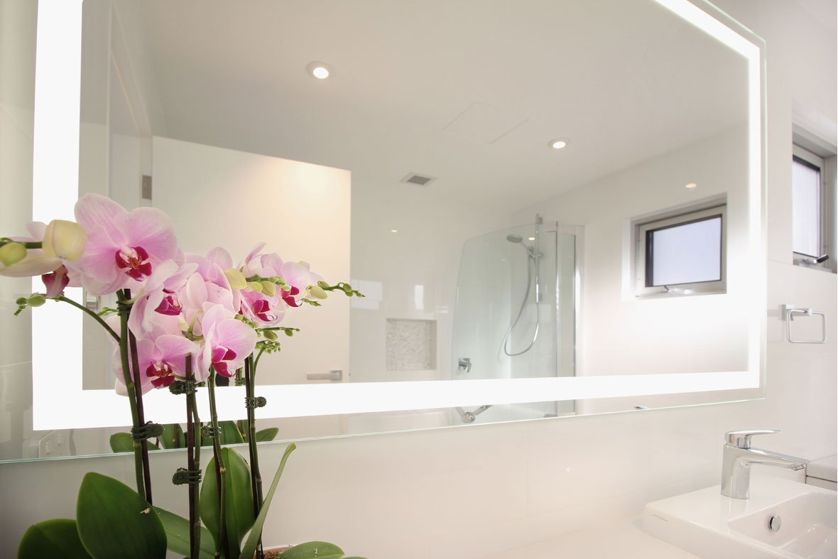 Verge Illuminated Mirror installed in a bathroom with white tiles