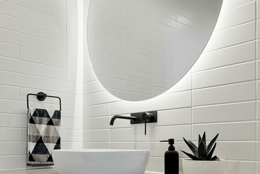 Halo Bathroom Lighted Mirror hanging above single sink Clearlight Designs