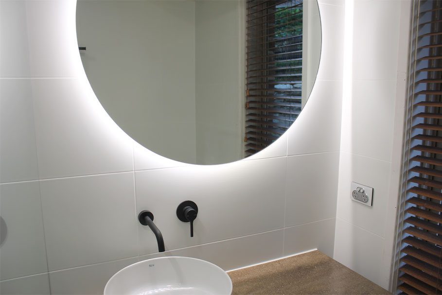Round Halo Bathroom Lighted Mirror hanging above single sink